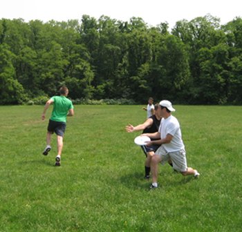 """Dark team member """"marks"""" white team member, who is trying to move the disc up the field."""