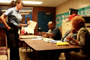 Officer Blackford hands the panel some relevant paperwork during a Youth Aid Panel meeting.
