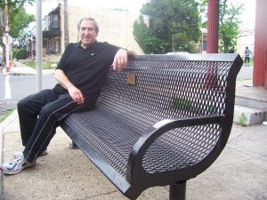 Arty Elgar sits on one of the benches he donated at the corner of 10th and Butler