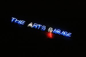 The neon sign hanging above the entrance to The Arts Garage.