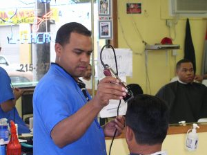 Antonio Cruz, owner of Los Brothers Barber Shop, diligently cuts his client's hair.