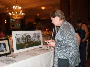 A guest looks at a silent auction item, a photograph of Laurel Hill Cemetery architecture.