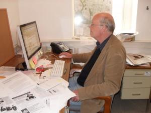 Karl Biemuller works at his desk.