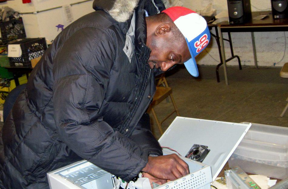 A Tech-Redi worker repairs a computer.