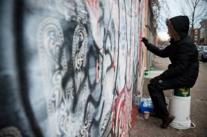 Cassady removes graffiti from the mural with special solvents.