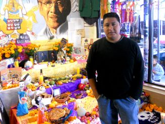 """Jair Andrade stood in front of the """"ofrenda"""" at the shop he owns."""