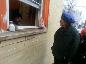 A volunteer from the Sister Peter Claver House talks to his guest through the open kitchen window.