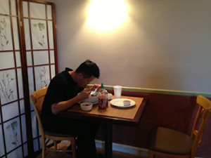 A waiter takes his break and enjoys a hot meal.