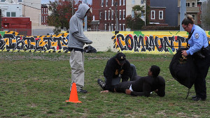 Antonio Sanchez, flanked by his coach, mother and friend, lies injured on the practice field after a hitting drill.