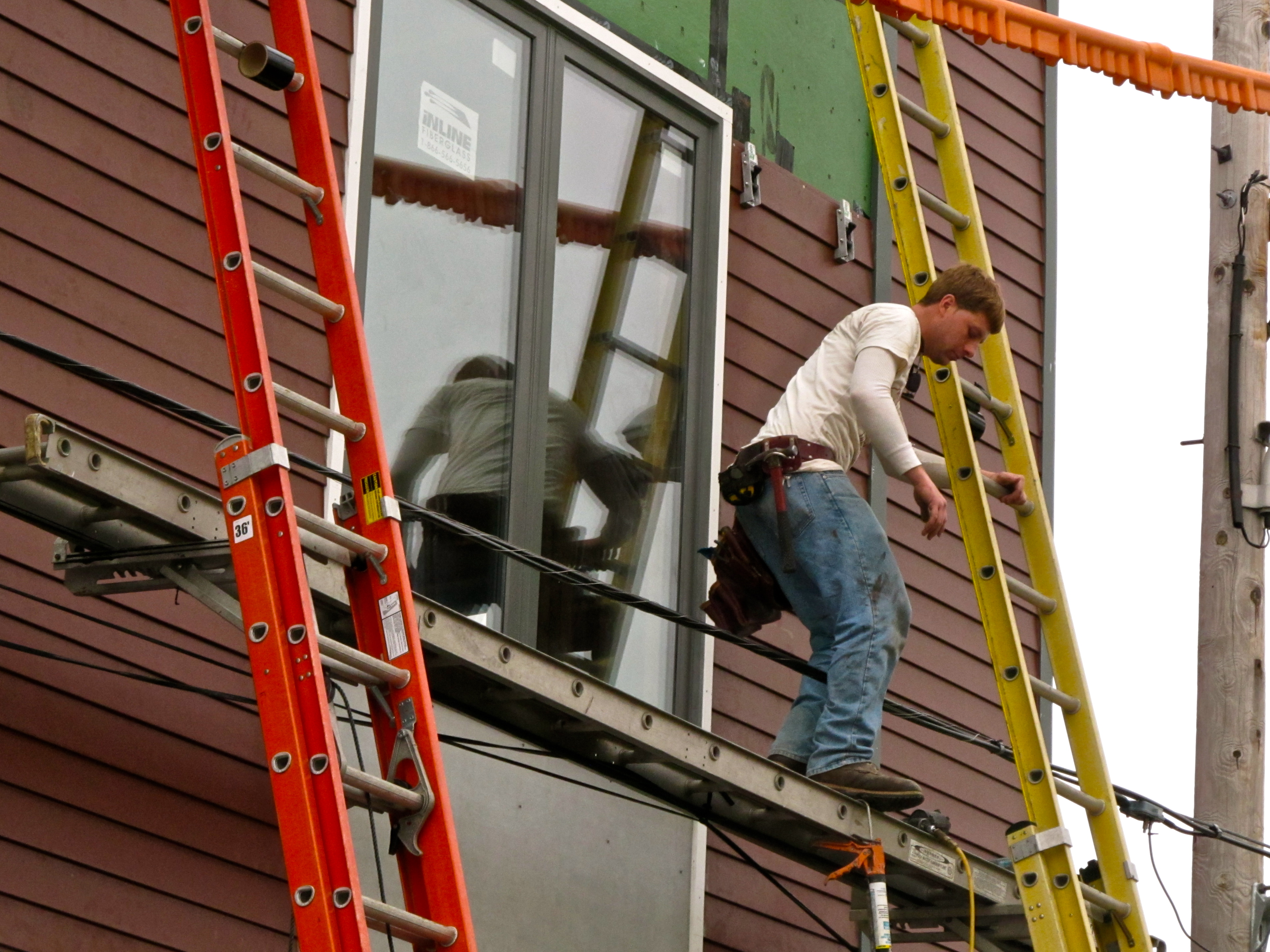 A construction worker for Postgreen Homes is working on the new condominium going up on Thompson St.