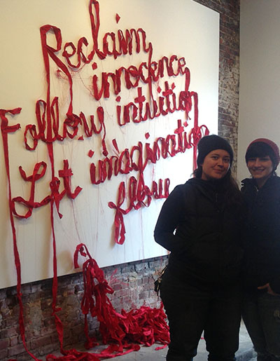 Owner Darla Jackson (left) and project manager Jenny Welsch (right) in front of artwork in the studio.