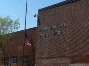The American flag waves in the wind outside Morton McMichael Elementary School.