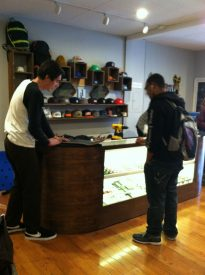 Sales representative at the Nocturnal Skate Shop helping a customer.