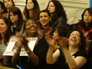 Parents applaud upon hearing students rally for school funding.