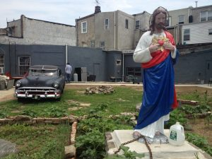 A statue of Jesus watches over a garden behind the Last Stop Clubhouse.