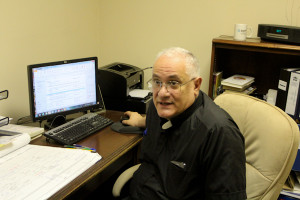 Father Domenic Rossi, the founder of Bethesda Project, working at his desk.