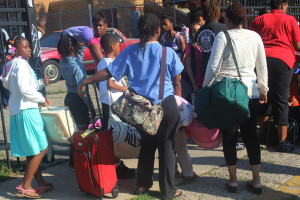 Kids lined up outside Helping Hands Rescue Mission waiting to board the bus to camp.