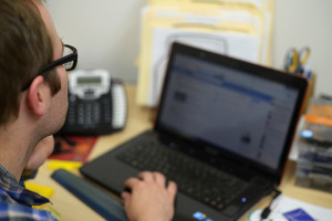 Marc Miller examines the stats on the back end of the circus school's Facebook page.