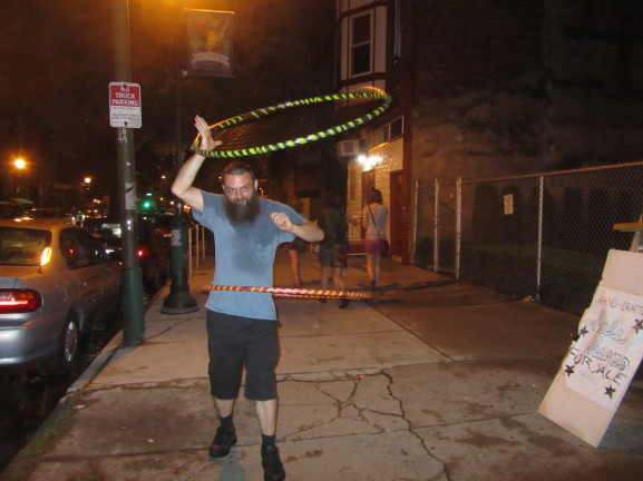Pete Tridish displayed his hula hoop skills in an effort to persuade passersby to try out and hopefully purchase his hand-made hoops.