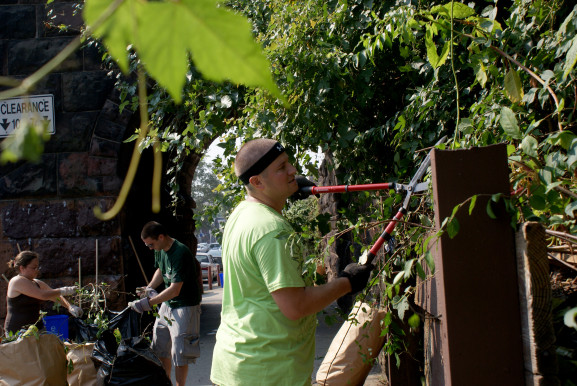 Larry Kovacs clips low-hanging vines near the railroad tunnel at Somerville and Fifth Streets in Olney.