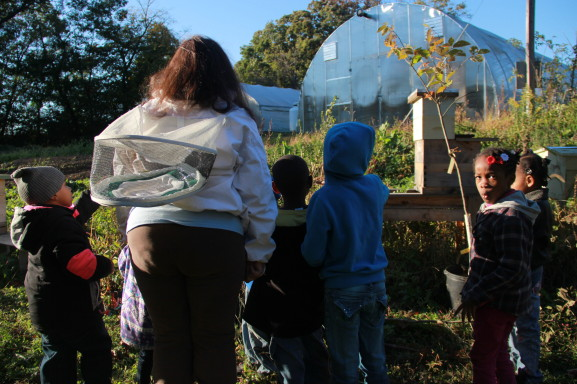 Beekeeper Anaiis Salles teaches children about beekeeping at the High Point Farm on Awbury Arboretum.