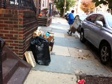 Trash bags and boxes line up the outside of a home's entryway. This is a ticket waiting to happen.