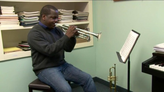 Thompson plays trumpet in his West Catholic Preparatory School office.