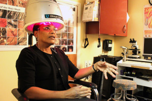 Pearl Bailey-Anderson demonstrates the ultimate hair laser, a device used for hair growth.