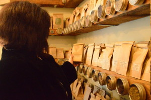 A woman reaches for a sack of herbs in Maia Toll's apothecary called The Herbiary in Chestnut Hill.