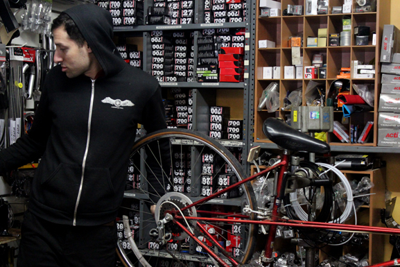 Nadav Carmel, an employee of Wolf Cycles, works on a bike during his downtime at the store.