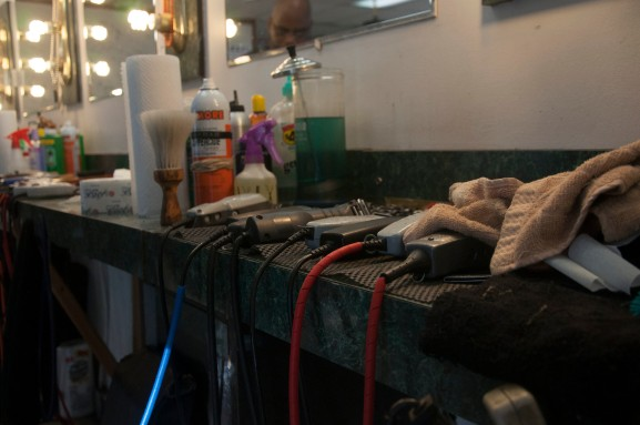 A quiver of hair clippers beside Nafis Williams as he spends his afternoon cutting hair and catching up with customers. | Photo: Michael Wojcik