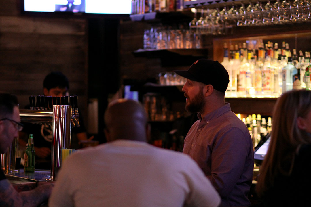 A barkeep at The Industry converses with patrons.