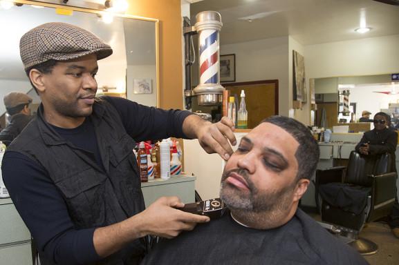 Barber and proprietor, Tachi Williams, left, shapes up the sideburns of Reginald McDermott at Shear Talent Barbershop.