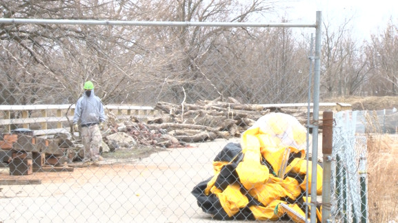 As winter gives way to spring, a lone construction worker walks past a collection of materials that, Scott Quitel says, will be preserved.