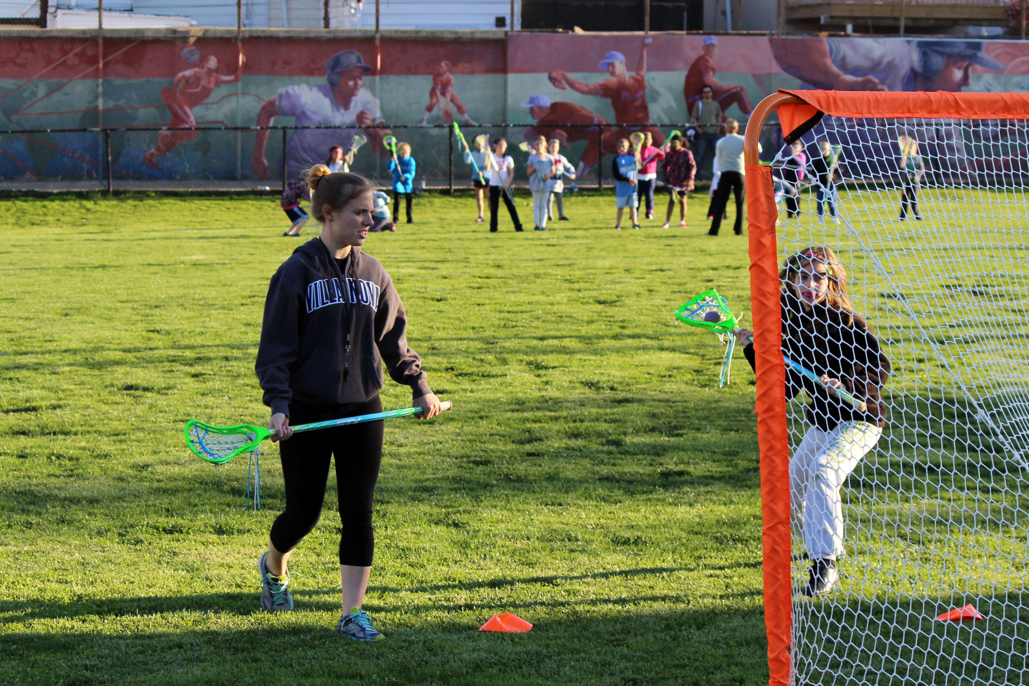 Jenna Allen, a lacrosse player from Villanova University, coaches the girls through a shooting drill.