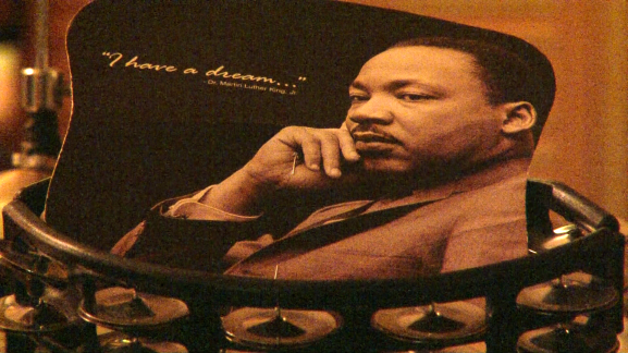 """A Martin Luther King, Jr. mousepad rests on top of a tambourine during a rehearsal of """"Behold the Man"""" by Evelyn Graves Drama Productions."""