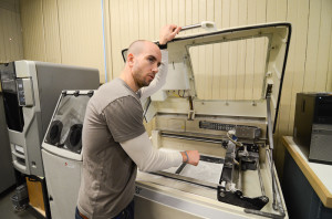 Jonathan Tekac displays the inner chamber of a gypsum sand 3D printer