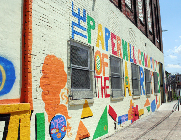 A painted mural on the outside of the PaperMill Community of Artists provides visitors with a glimpse of the various imaginative characteristics of the work found inside.