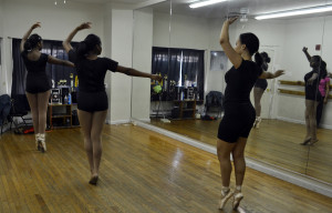 Two dancers practice their ballet moves for the routine.