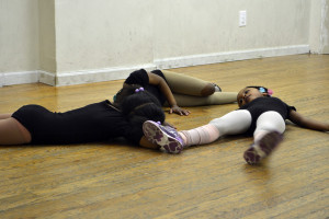After a long day of practice, the dancers lie on the floor to relax.