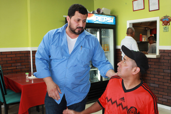 Orlando Guevara (right) often watches World Cup games at work.