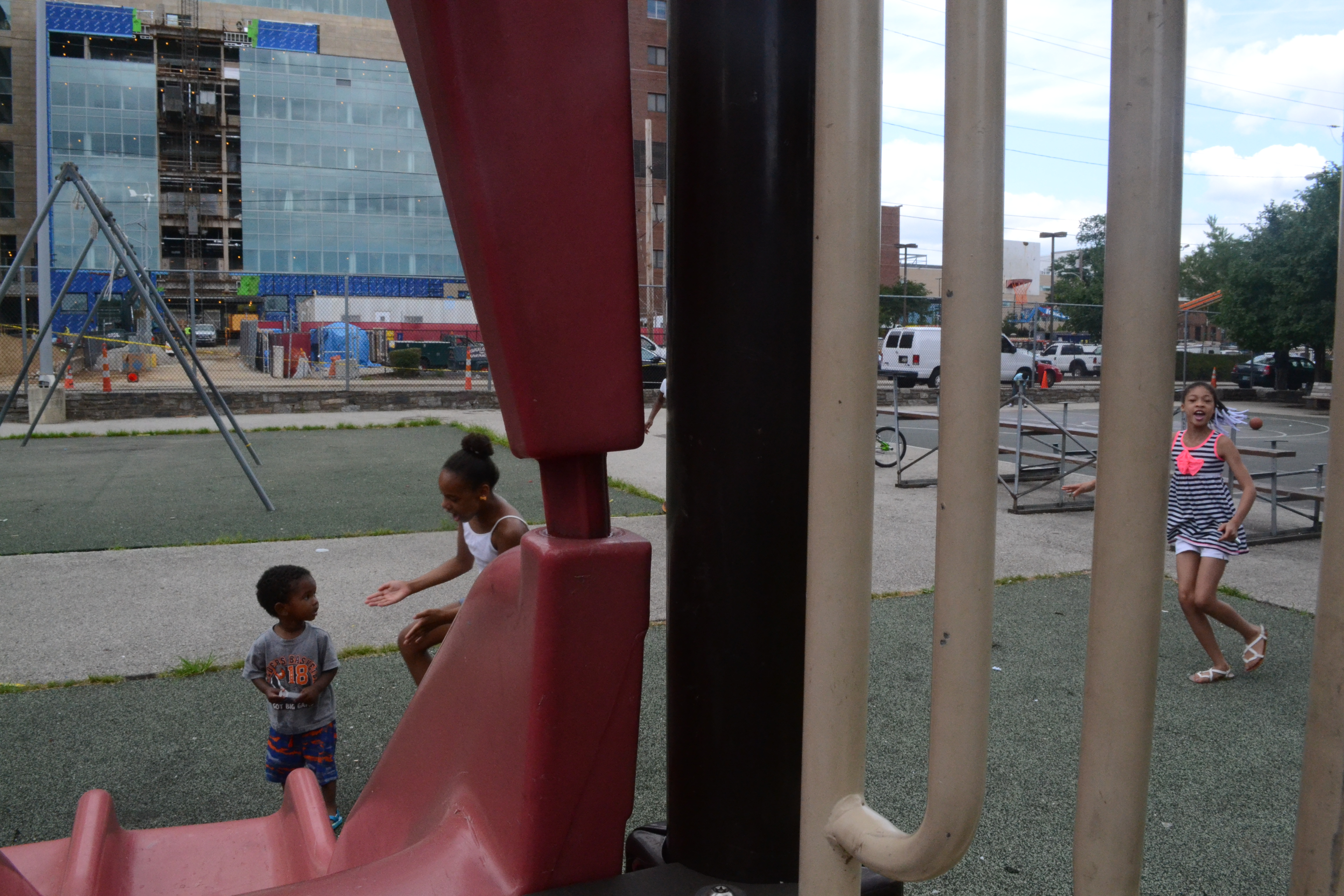 Children play at the Norris Apartments playground as construction continues on Temples New Life Sciences Building. Photo/Mamaye Mesfin
