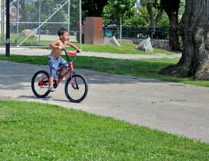 A child rides his bike through McPherson Square Park.