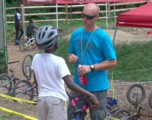 Kenn Rymdeko, founder and project manager for Philly Pumptrack, works with kid after taking test to advance to bigger course.