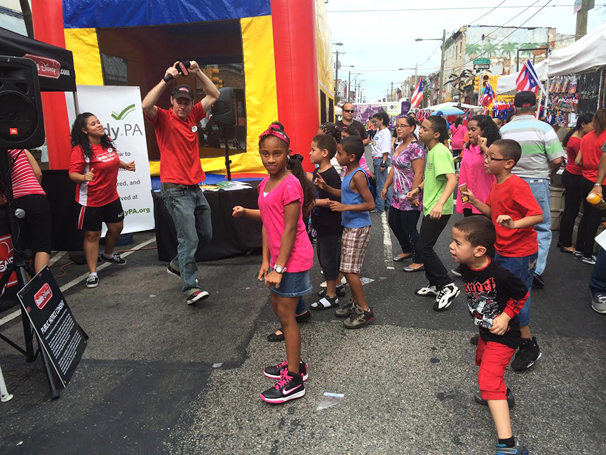 Children at the celebration learning a dance and getting involved in the festivities.