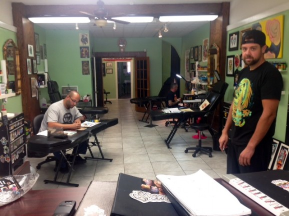 Inkwell 215 artists Evan Clark and Matt Solomon create custom designs for clients while Mike Nemo looks on .