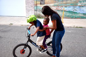 Courtney Young and her two children, Chase and Carter play outside on their street in Point Breeze.