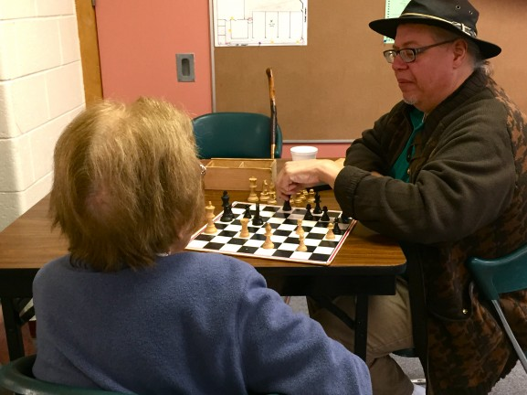 Some of the adults prefer to play a game of chess and relax with friends.