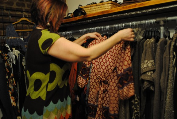 Mary fixing a shirt hanging on a rack.