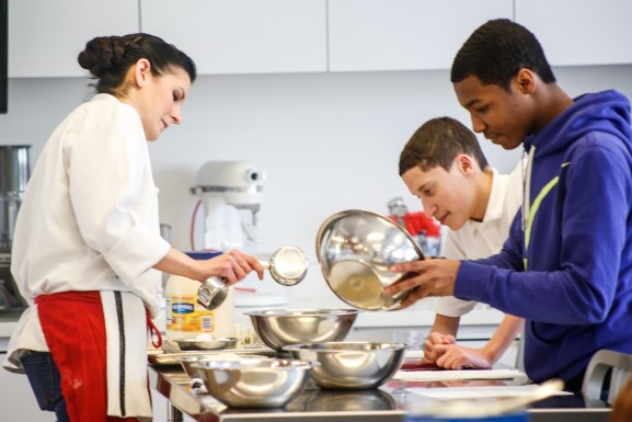 Chef Carla Norelli helps some students measure out their ingredients.